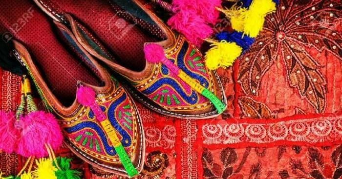 Traditional shoes on display with colorful background in Jaipur