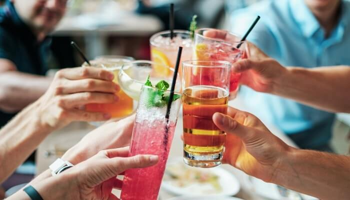 People taking off their glasses with cocktails and mocktails