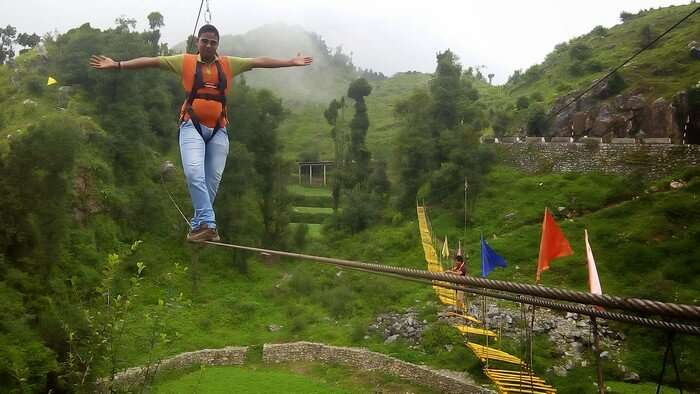 An adventure enthusiast tries to balance on the skywalk