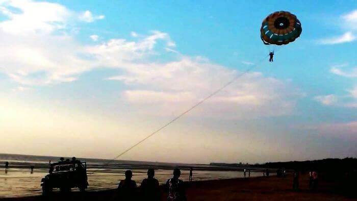 A person enjoys parasailing on a lovely evening at Jampore Beach