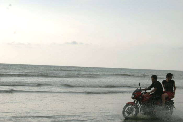 A couple enjoys a bike ride on a lovely evening at the Muzhappilangad Beach