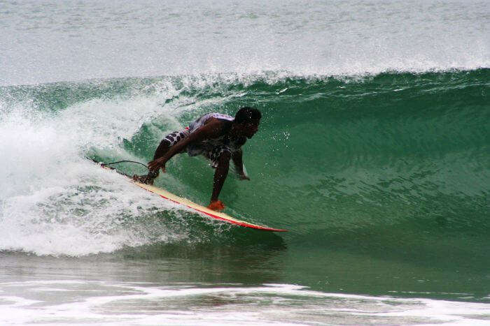 A young man surfs on the waves at the Covelong Beach