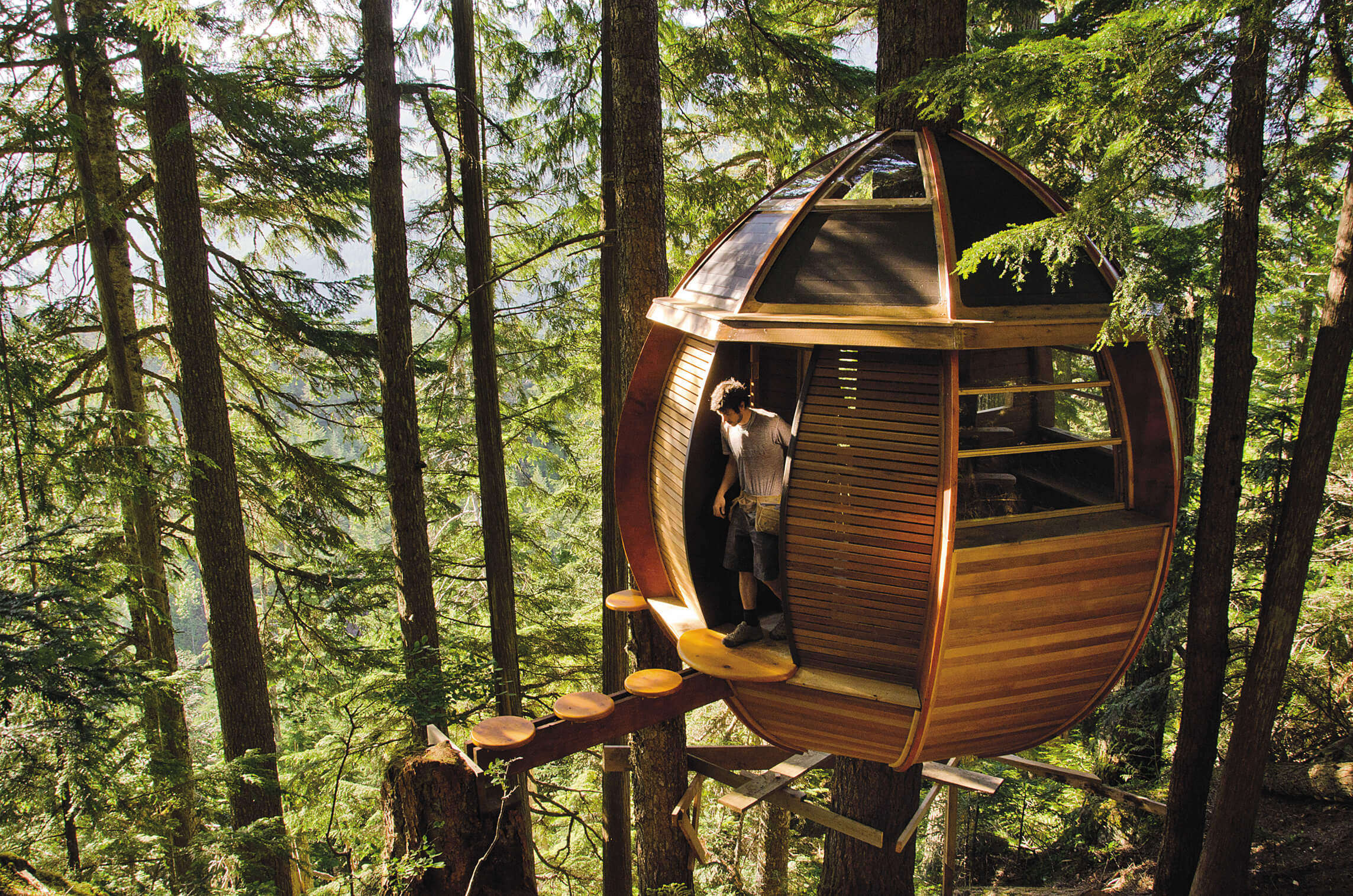A man coming out of the Hemloft Treehouse in Whistler in Canada